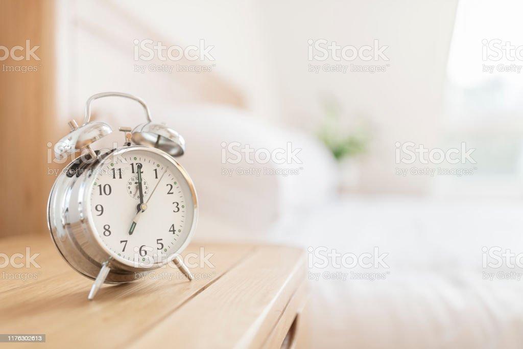 Alarm clock morning wake-up time Alarm clock morning wake-up time on bedside table with copy space Alarm Stock Photo