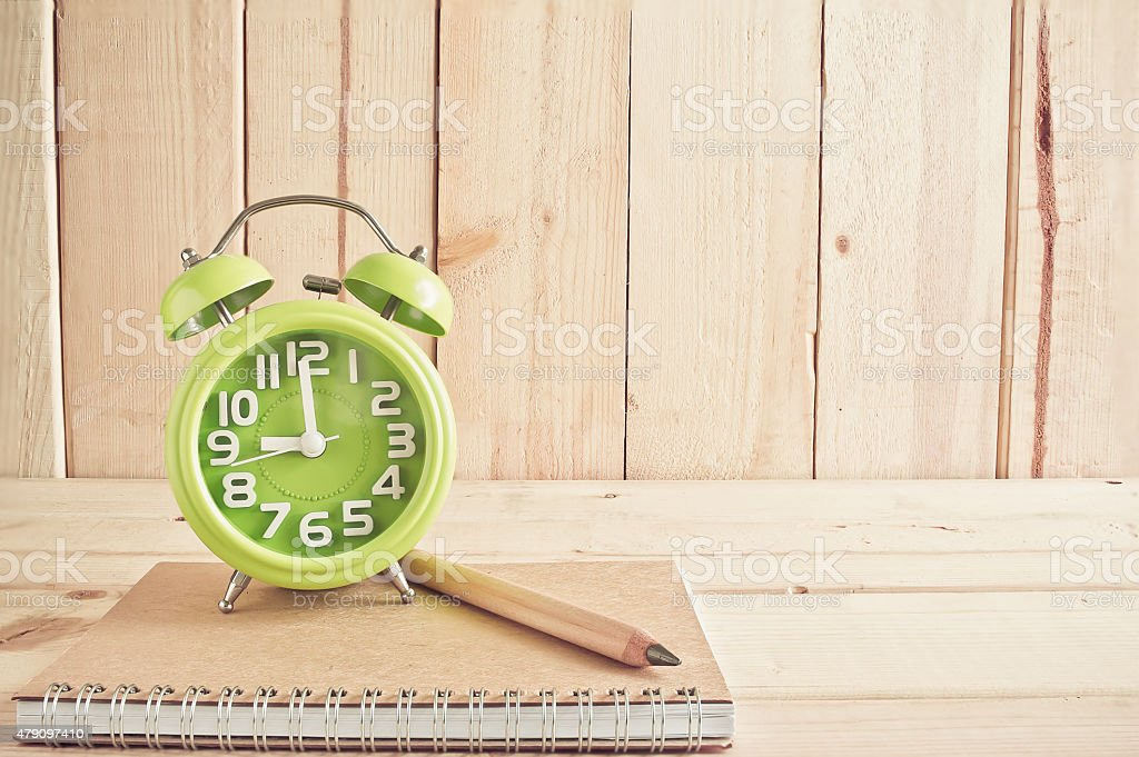 Alarm clock , notebook and pencil on wooden table stock photo
