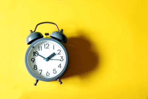 Wecker auf einem leuchtend gelben Hintergrund, Zeit-Management-Konzept – Foto