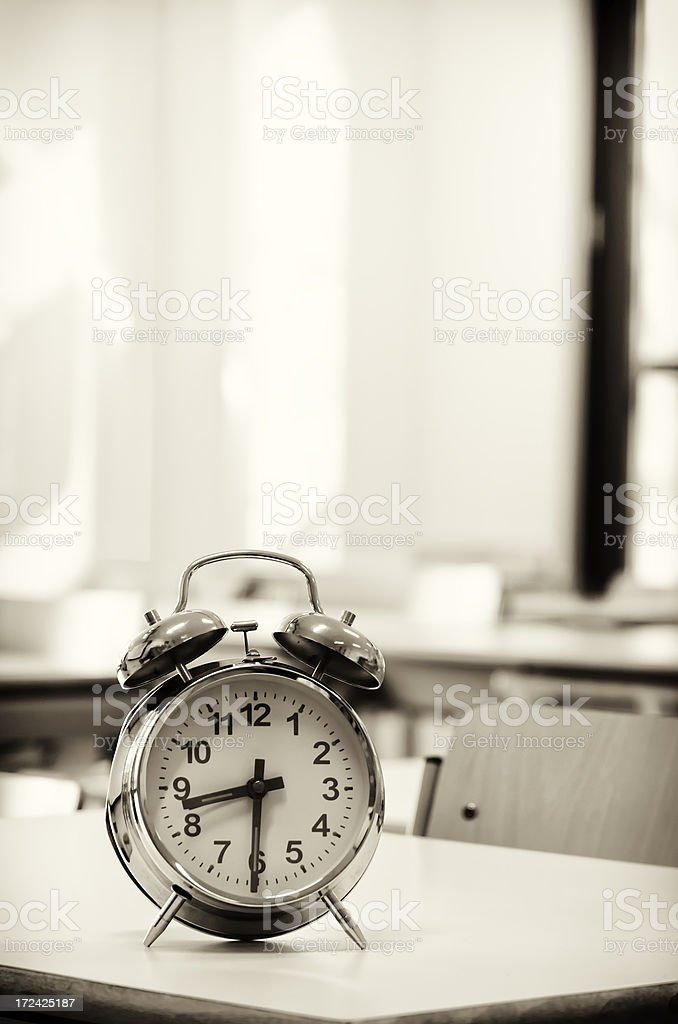 Alarm clock on a desk in class room royalty-free stock photo