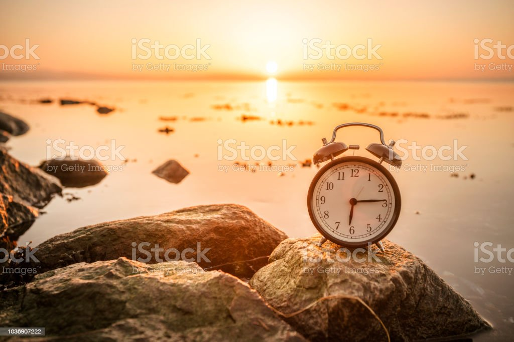 Alarm clock on a rock in the sunrise by the ocean stock photo