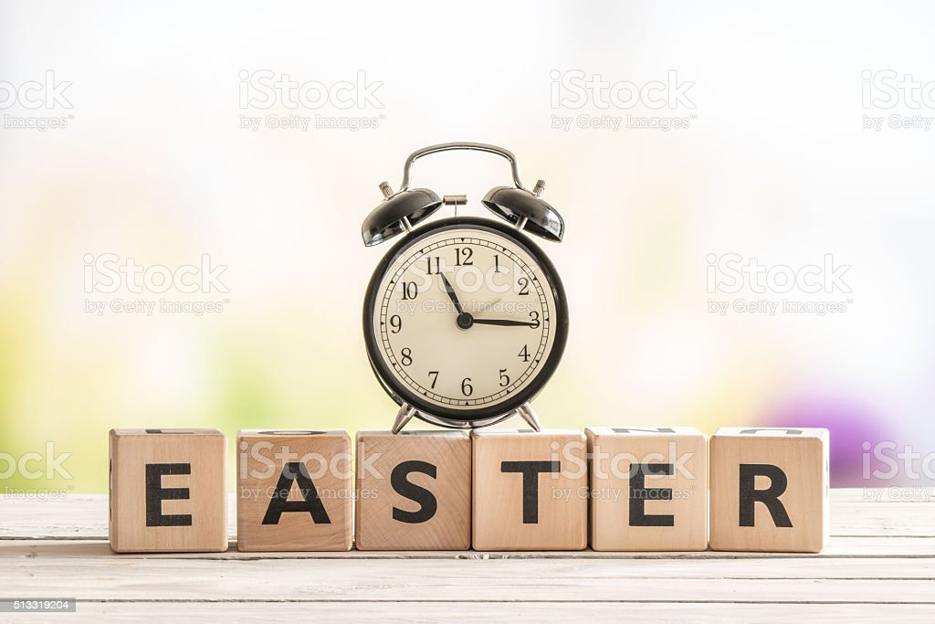 Alarm clock on a wooden easter sign stock photo