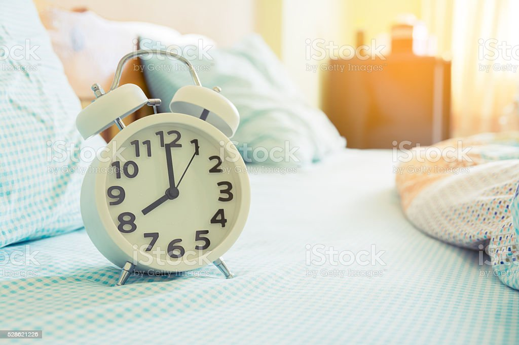 Alarm Clock On Bed In Morning Stock Image