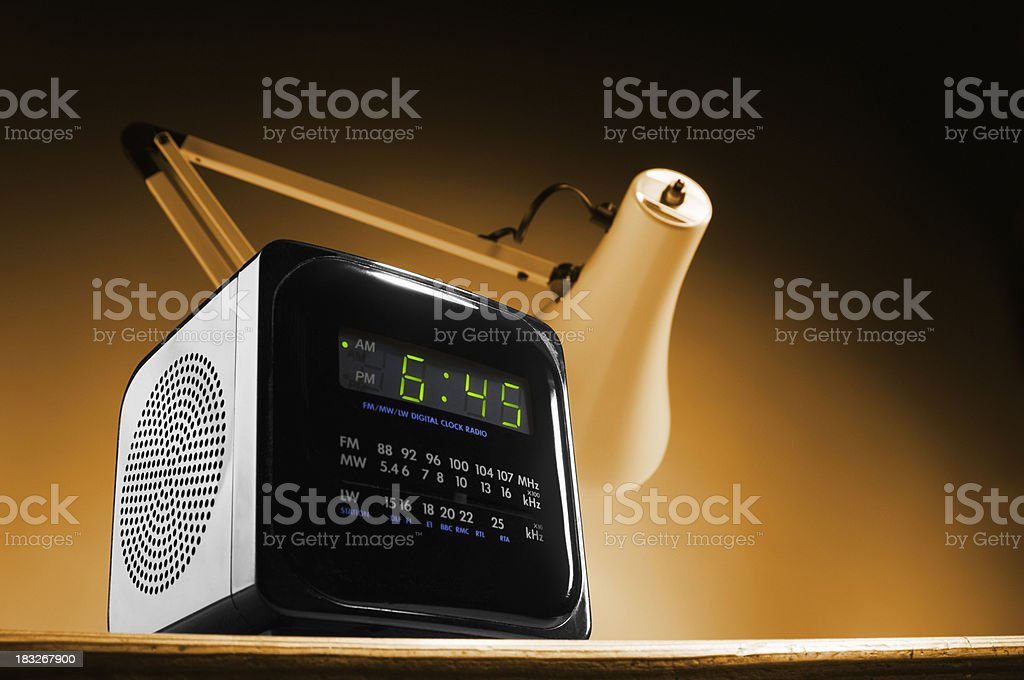 Alarm clock on bedside table with reading lamp stock photo