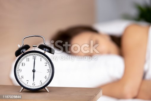 istock Alarm clock on bedside table with woman sleeping on background 1157025844