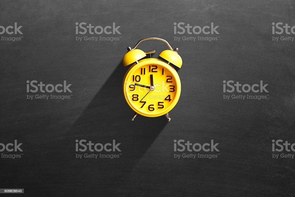 Alarm clock on blackboard stock photo