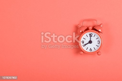 istock Alarm clock on coral background. 1078267902
