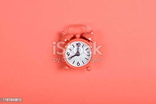 istock Alarm clock on coral background. 1181640612
