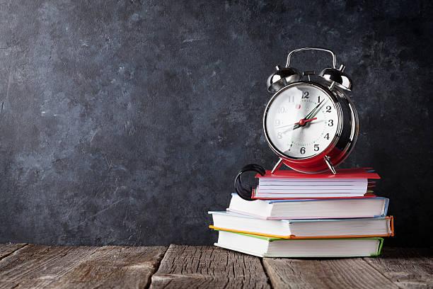 alarm clock on notepads in front of chalk boad - kreide farbe schreibtisch stock-fotos und bilder
