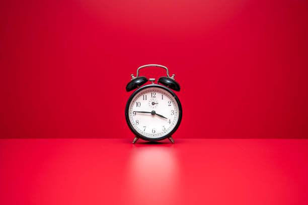 Alarm clock on red background stock photo