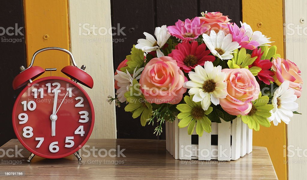 alarm clock on table with flower royalty-free stock photo