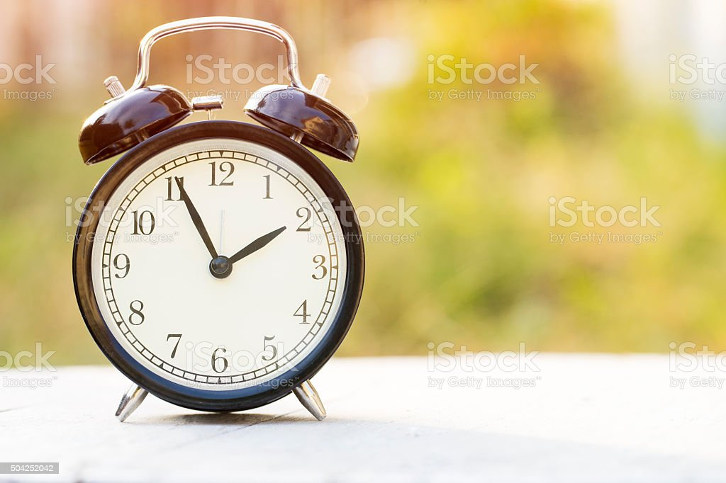alarm clock on table with green background stock photo