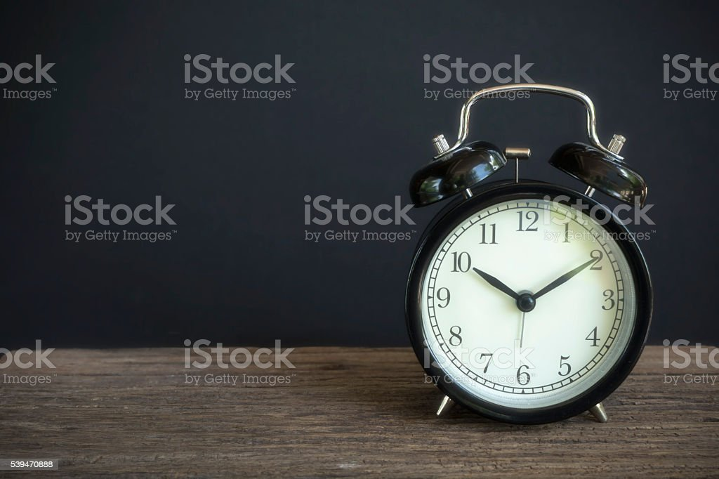 Alarm clock on wood with a black background stock photo