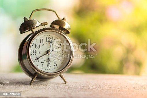 istock alarm clock on wooden table with morning background 1061556228