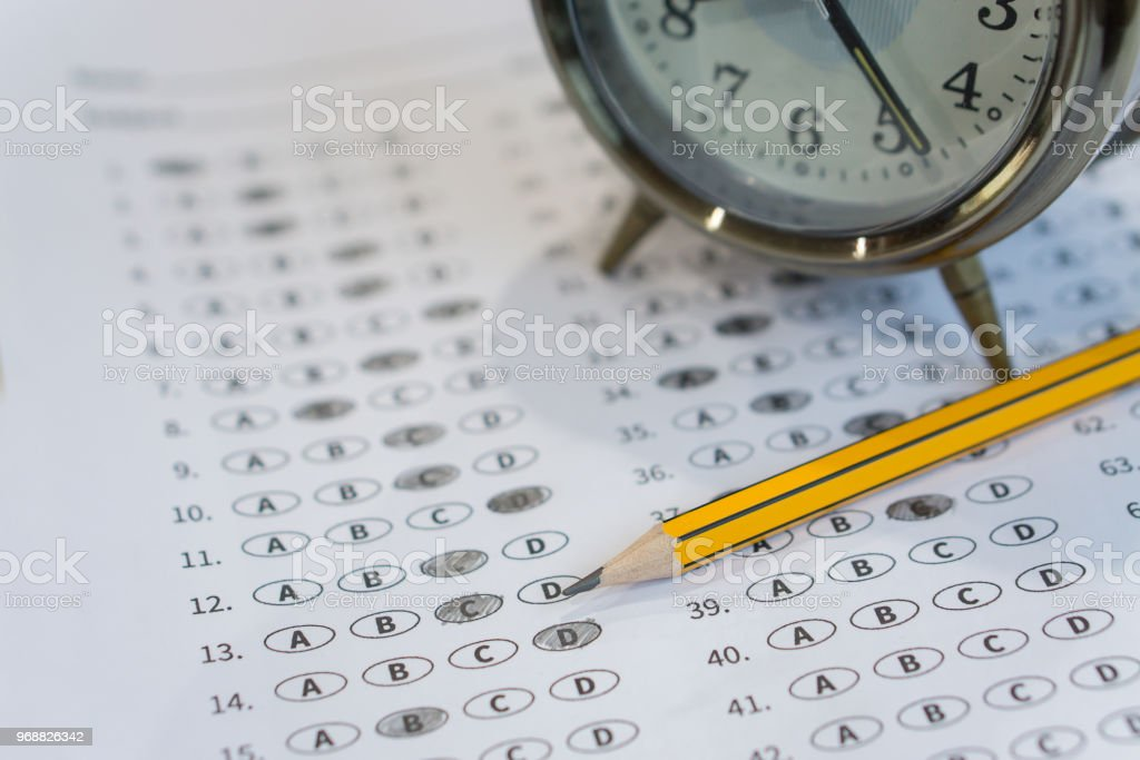 alarm clock, optical form of standardized test with bubbled and a black pencil examination,Answer sheet,education concept,selective focus,vintage color stock photo