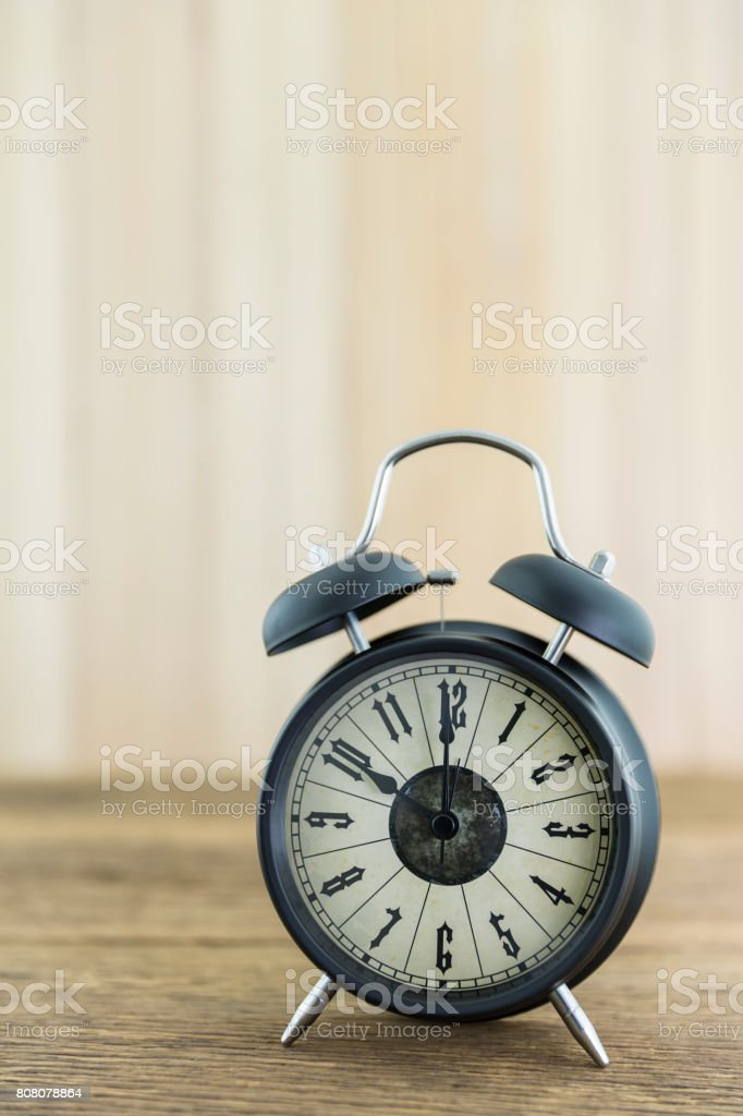 Alarm clock placed on a piece of rough wood stock photo