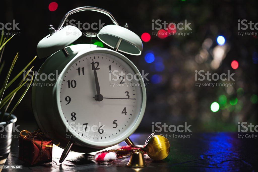 Alarm clock show last minute before midnight with ornaments for...