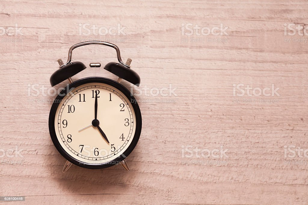 Alarm clock showing five o'clock on wooden background stock photo