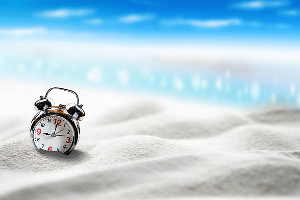 Alarm clock sink to sand on beach side blue sky. – Foto