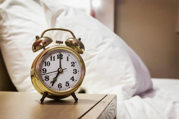Wecker steht auf einem Nachttisch im Zimmer – Foto
