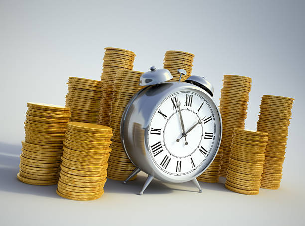Alarm clock surrounded with coins stock photo