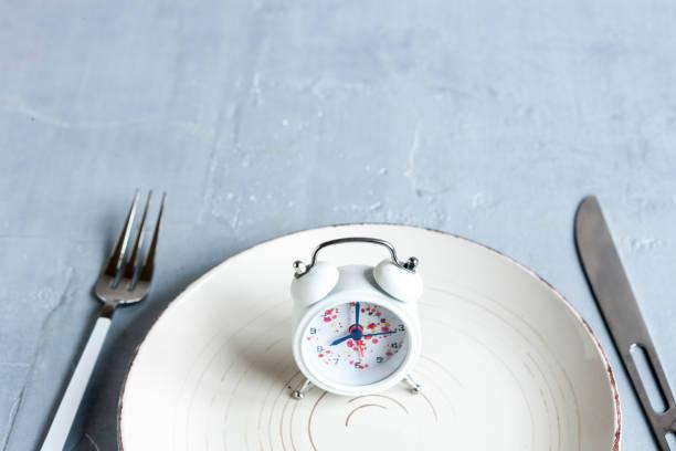 Despertador, placa branca com garfo e faca, conceito de jejum intermitente, dieta cetogênica, perda de peso - foto de acervo
