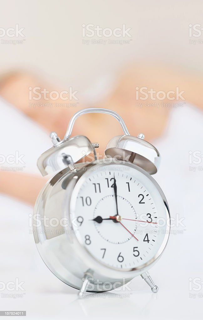 Alarm clock with a girl sleeping at the back royalty-free stock photo