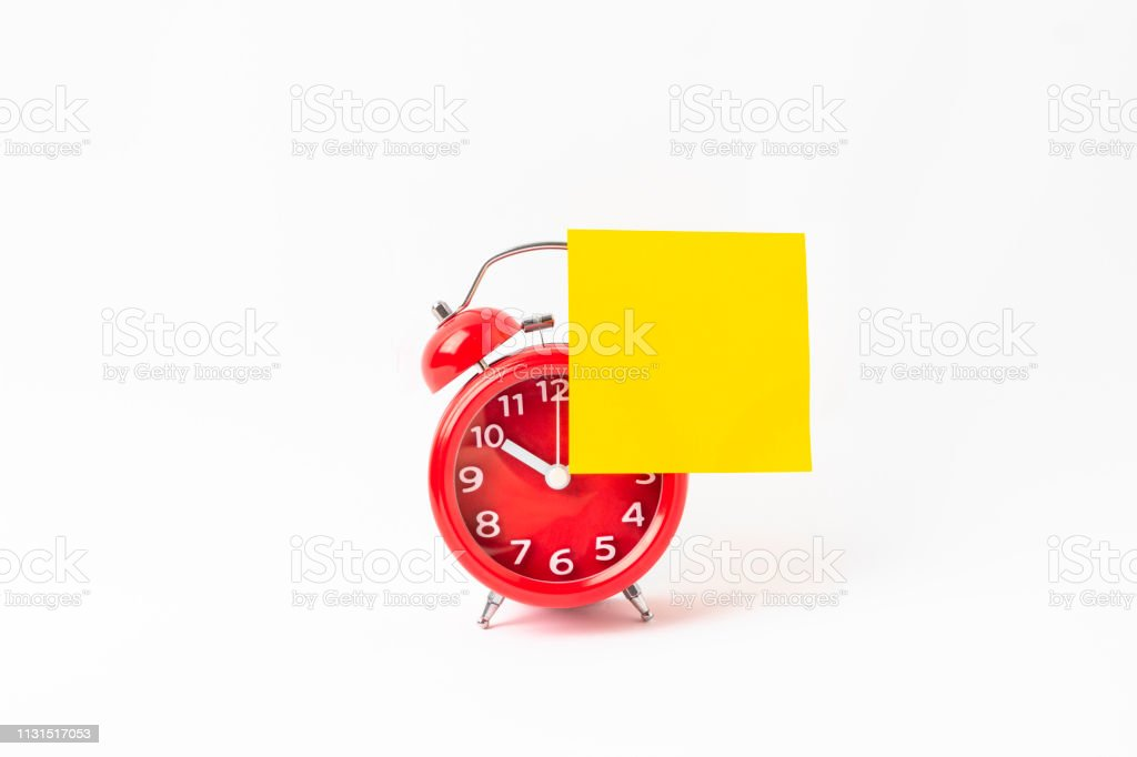 Alarm clock with a yellow sticky paper. stock photo
