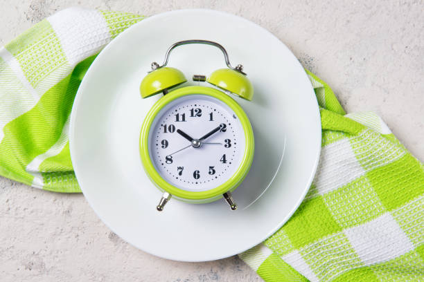 Alarm clock with bells on the plate, lunch time concept, top view with copy space stock photo