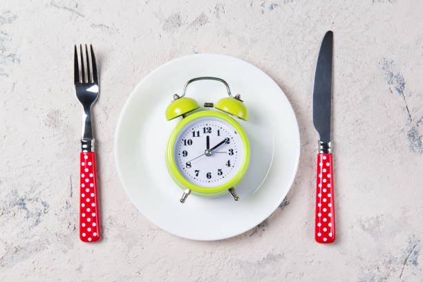 Alarm clock with bells on the plate with fork and knife, lunch time concept, top view with copy space stock photo