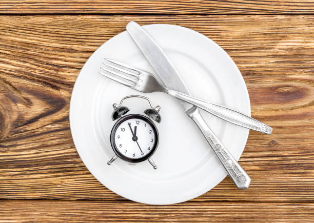 Alarm clock with fork, knife and plate on the table. Top view. Time to eat. stock photo