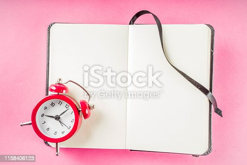 1090161334 istock photo Alarm clock with notepad on bright pink table 1158406123