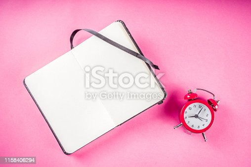 1090161334 istock photo Alarm clock with notepad on bright pink table 1158406294