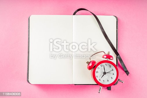 1090161334 istock photo Alarm clock with notepad on bright pink table 1158406305