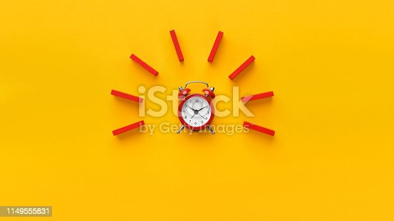 istock Alarm clock with red dominoes on yellow background 1149555831
