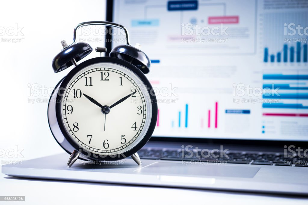 Alarm clock with stock graph chart in laptop screen background. stock photo