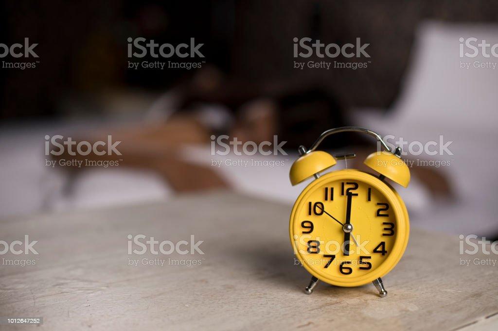 Wecker mit Frau schläft auf Bett – Foto