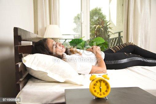 istock Alarm clock with woman sleeping on bed 974968606