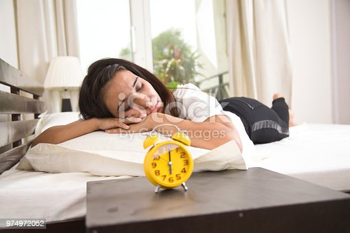 istock Alarm clock with woman sleeping on bed 974972052