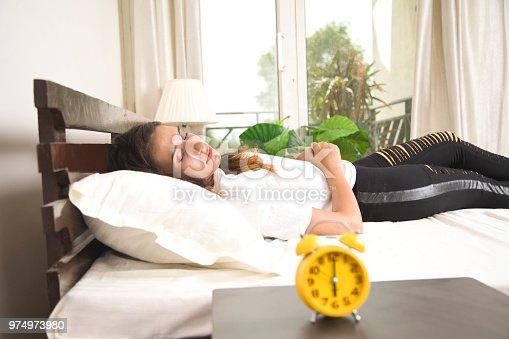 istock Alarm clock with woman sleeping on bed 974973980