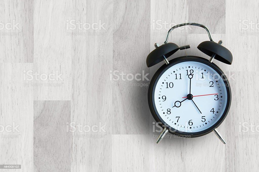 Alarm clock with wooden floor stock photo