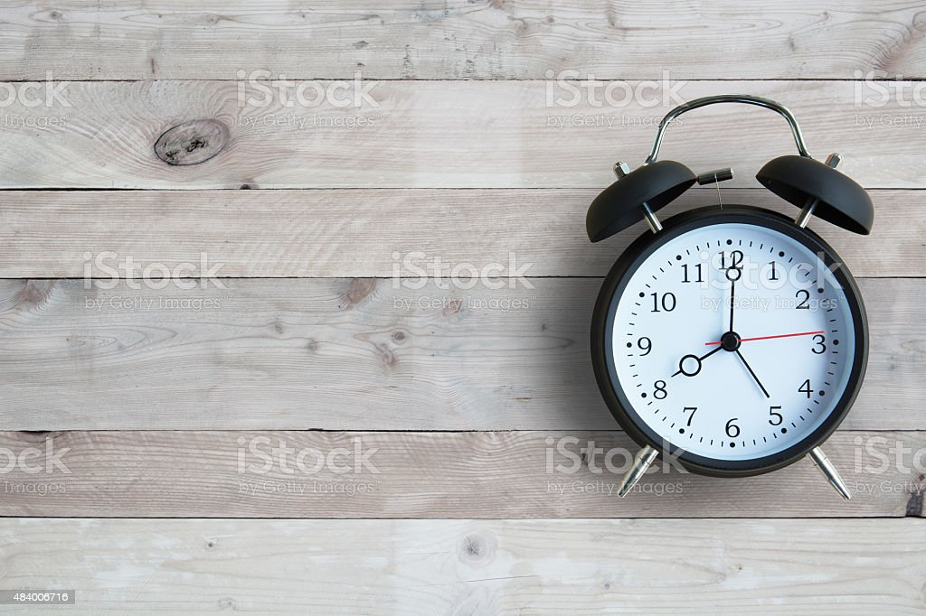 Alarm clock with wooden floor stock photo