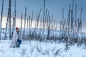 Caucasian charmed woman dressed in warm winter clothing. The woman is stepping through the deep snow. She is looking anxiously aside. Shooting outdoors at cold winter day in a dead birch forest with dramatic sky as the background