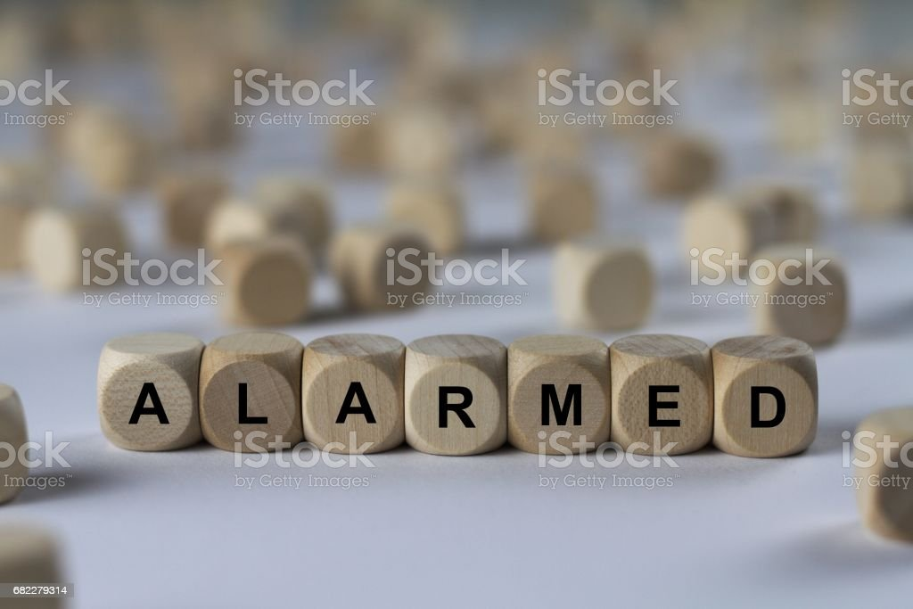 alarmed - cube with letters, sign with wooden cubes stock photo