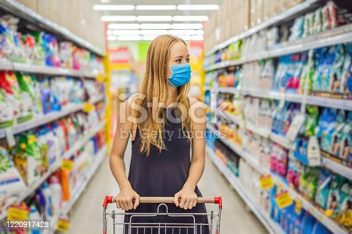 istock Alarmed female wears medical mask against coronavirus while grocery shopping in supermarket or store- health, safety and pandemic concept - young woman wearing protective mask and stockpiling food 1220917428