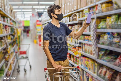 istock Alarmed man wears medical mask against coronavirus while grocery shopping in supermarket or store- health, safety and pandemic concept - young woman wearing protective mask and stockpiling food 1220917394