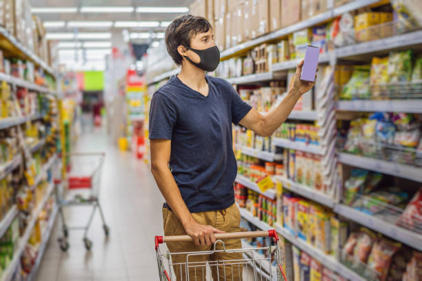 alarmed man wears medical mask against coronavirus while grocery shopping in supermarket or store- health, safety and pandemic concept - young woman wearing protective mask and stockpiling food - bazar mercato foto e immagini stock