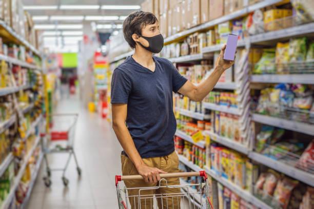 슈퍼마켓이나 상점에서 식료품 쇼핑하는 동안 경보 남자는 코로나 바이러스에 대한 의료 마스크를 착용 - 건강, 안전 및 전염병 개념 - 젊은 여성은 보호 마스크를 착용하고 음식을 비축 - 바자 뉴스 사진 이미지