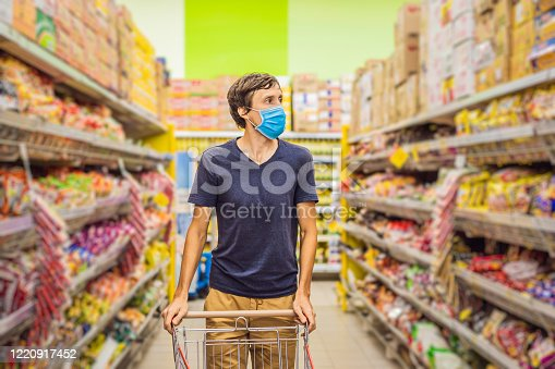 istock Alarmed man wears medical mask against coronavirus while grocery shopping in supermarket or store- health, safety and pandemic concept - young woman wearing protective mask and stockpiling food 1220917452