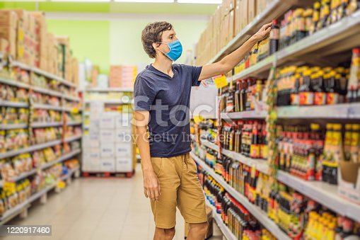 istock Alarmed man wears medical mask against coronavirus while grocery shopping in supermarket or store- health, safety and pandemic concept - young woman wearing protective mask and stockpiling food 1220917460